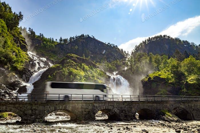 Tourist bus traveling on the road Latefossen Waterfall Odda Norw