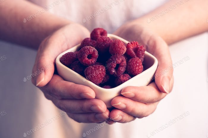 Woman offering a bowl of raspberries