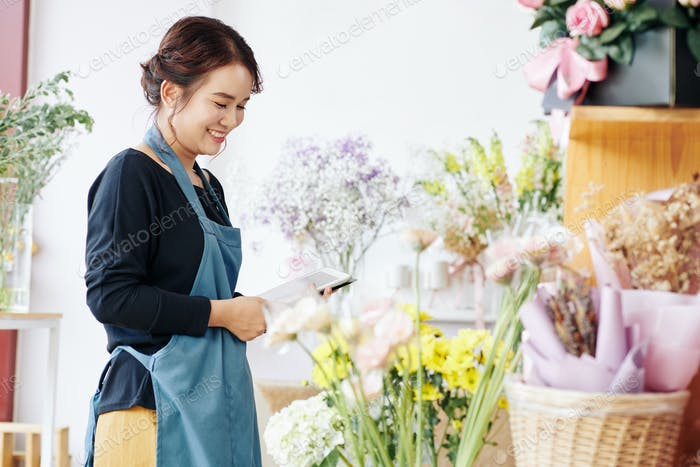 Smiling florist checking flowers in shop