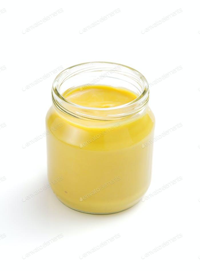 mustard sauce in jar on white