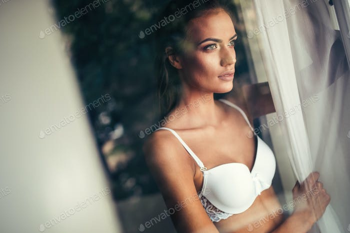Beautiful alluring young woman in sexy white lingerie with glamorous face