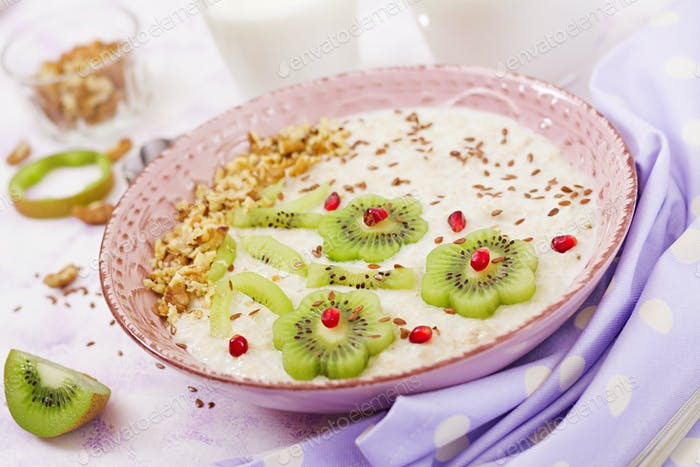 Tasty and healthy oatmeal porridge with kiwi, pomegranate and nuts