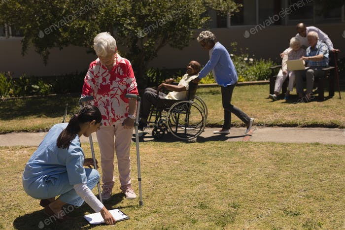 Young female doctor kneeling and examining in front of disabled senior woman in garden