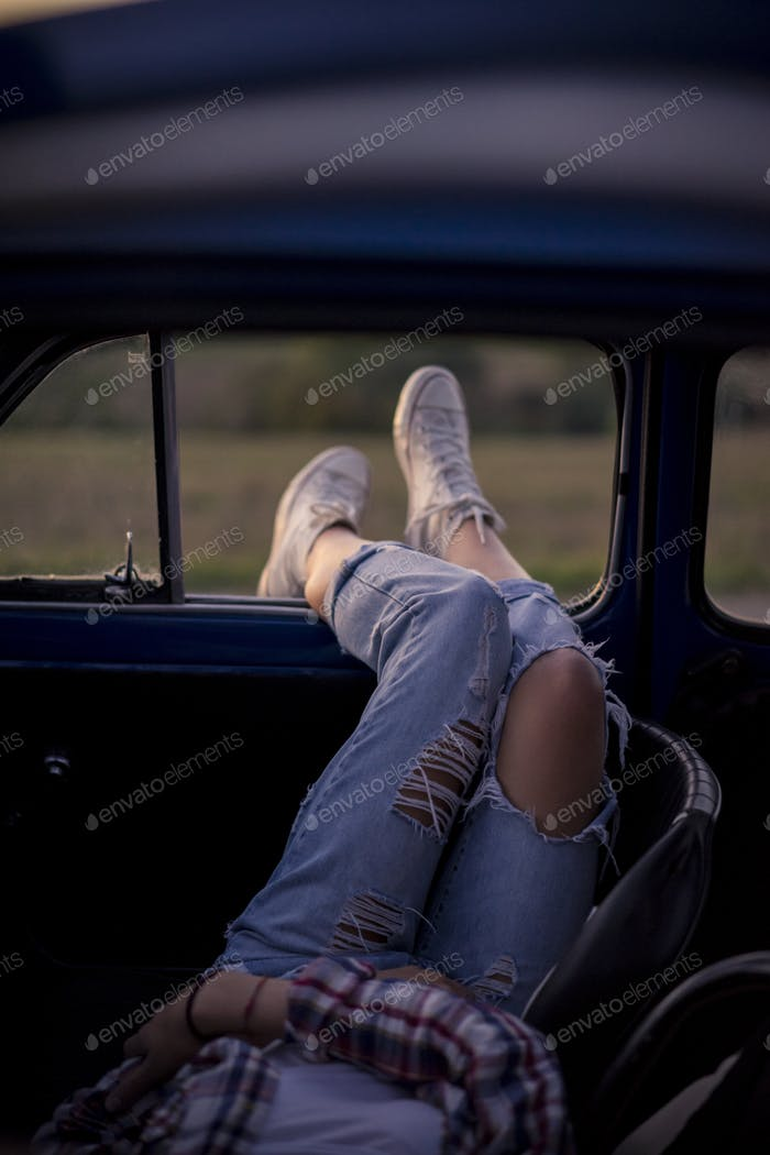 Young woman relaxing in a Vintage Car