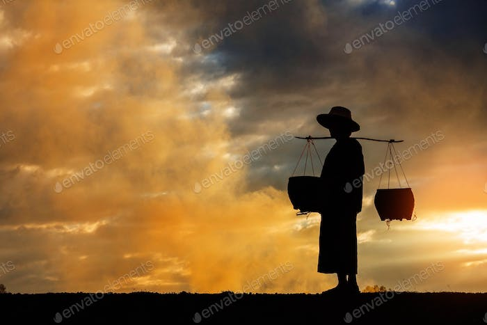farmer walking at sunset