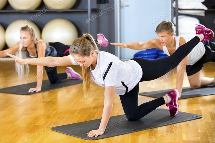 Frau in Sportbekleidung Training mit Freunden auf Matten