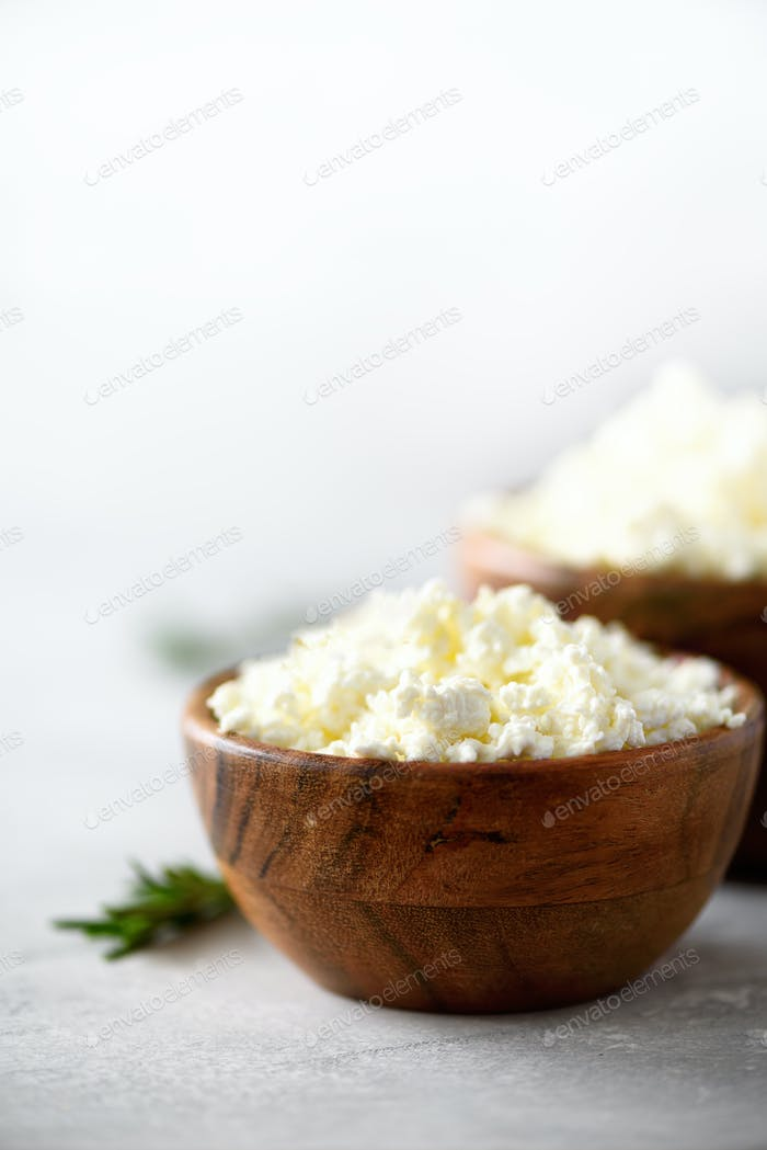 Homemade cottage cheese in wooden bowl, green rosemary on grey background. Copy space