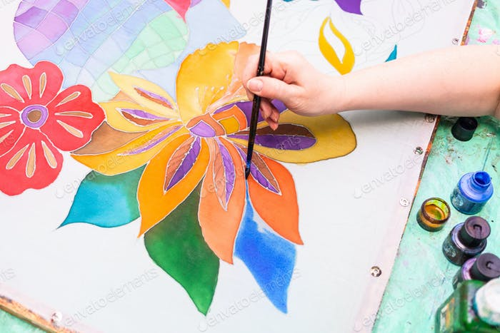 artist paints batik with floral pattern on silk