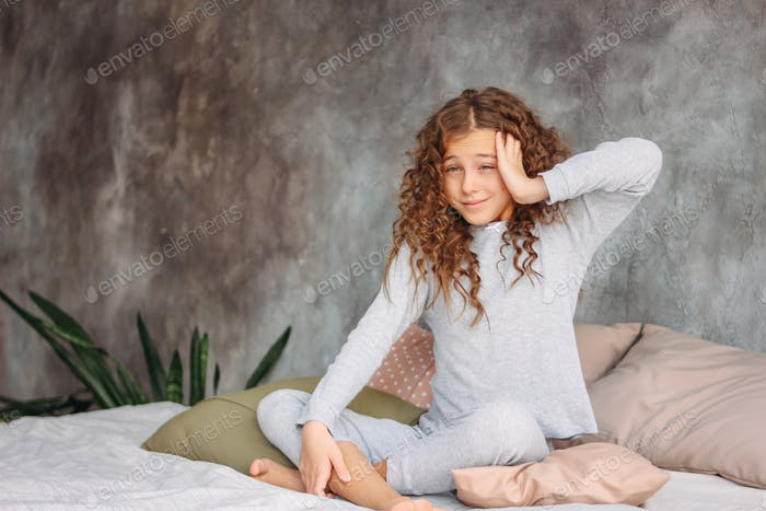 Curly haired tween girl in pajamas just waking up and sitting on bed with pillow