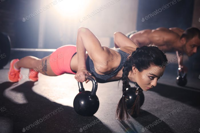 Couple doing push ups with kettlebells