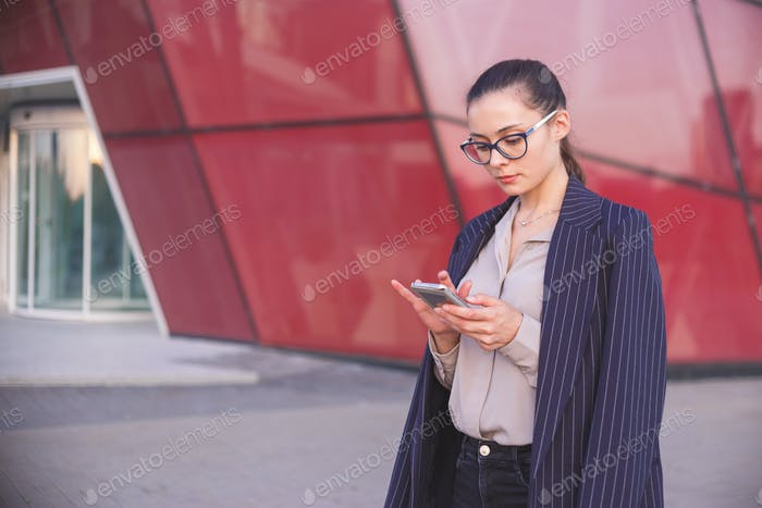 Young brunette woman in suit with smartphone