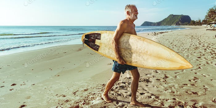 A man with a surfboard by the coast