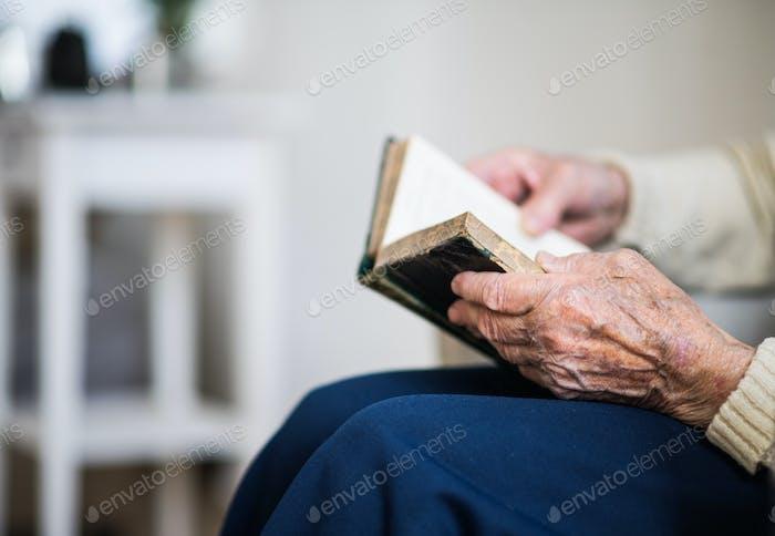 Eine Nahaufnahme von Senior Frau, die die Bibel zu Hause liest.