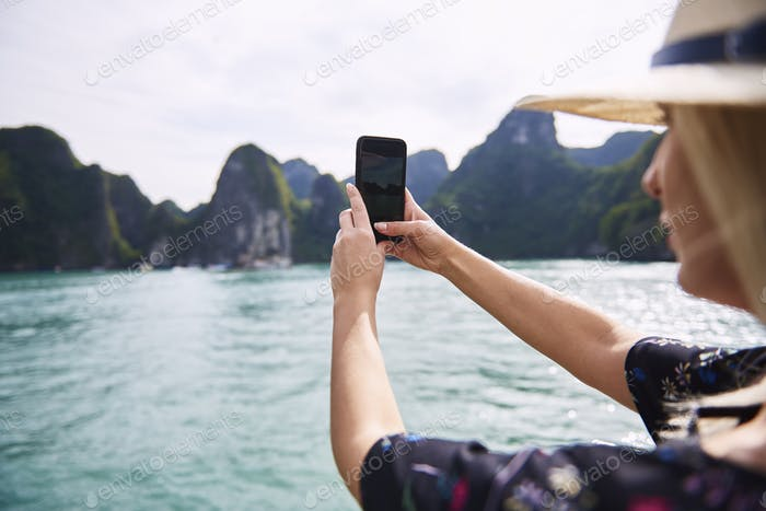 Woman photographing rock formations in Ha Long Bay Vietnam