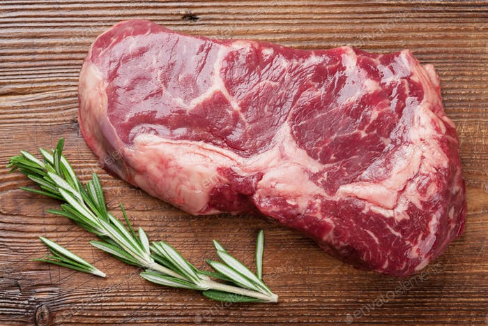 Raw ribeye beef steak cooking with rosemary