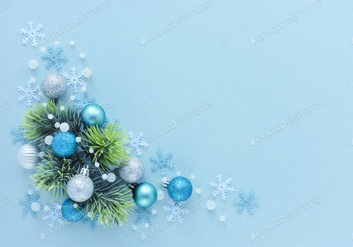 Spruce branches and christmas decorations on pastel blue background
