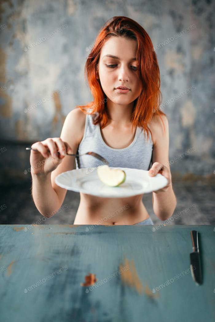 Female person against plate with a slice of apple