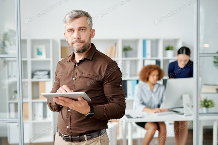 Serious businessman in smart casual looking at you in office environment