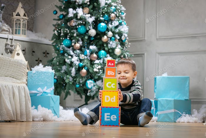 Preschool boy playing with wooden alphabet blocks against Christmas tree