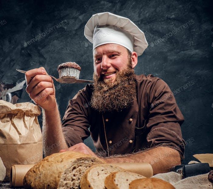 Panadero barbudo feliz con su trabajo, mirando su muffin recién hecho mientras se apoya en una mesa