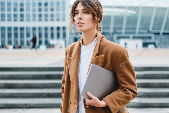 Young attractive stylish businesswoman in coat with laptop dreamily looking away on city street
