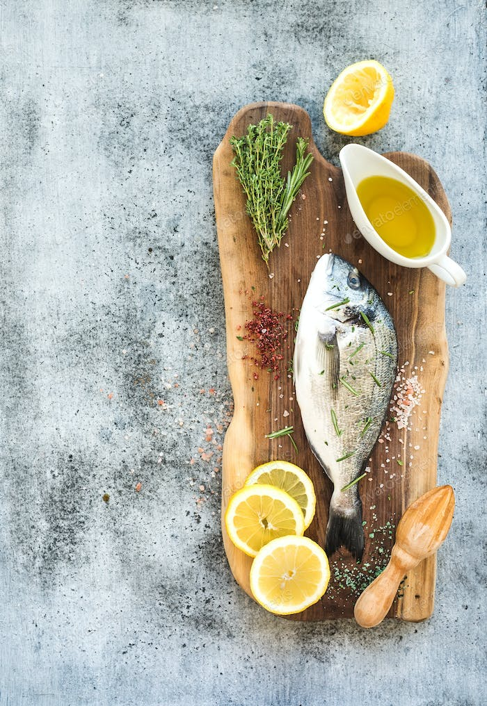 Fresh uncooked dorado or sea bream fish with lemon, herbs, oil and spices on rustic wooden board