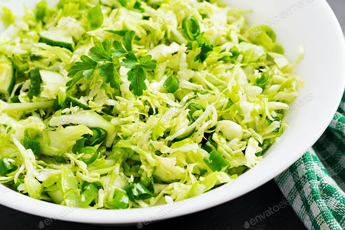 Vegetarischer Salat. Frühlings-Salat mit Kohl, Gurke, Frühlingszwiebel und Petersilie.