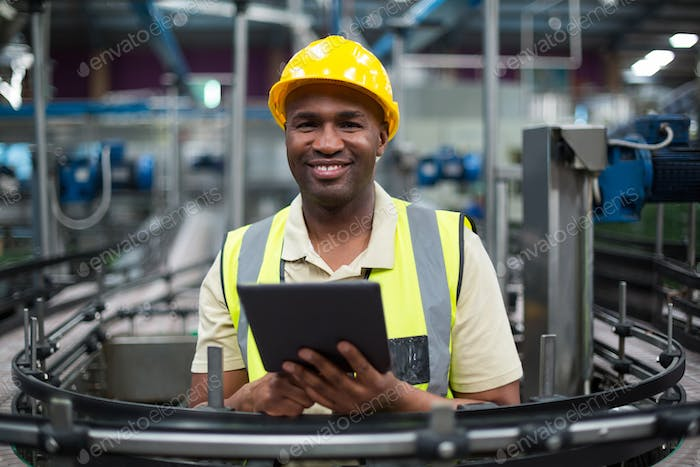 Smiling factory worker using a digital tablet in the factory