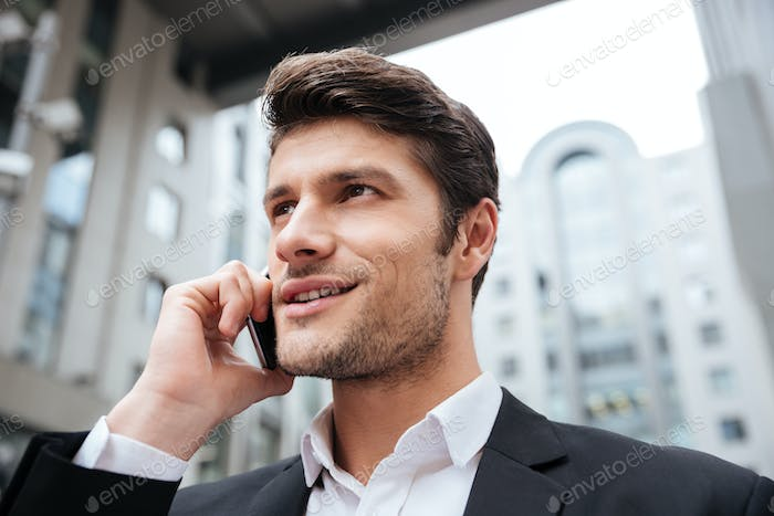 Cheerful attractive young businessman talking on cell phone outdoors