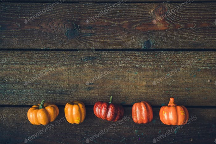 Creative layout of colorful pupmkins against wooden background. Halloween concept.