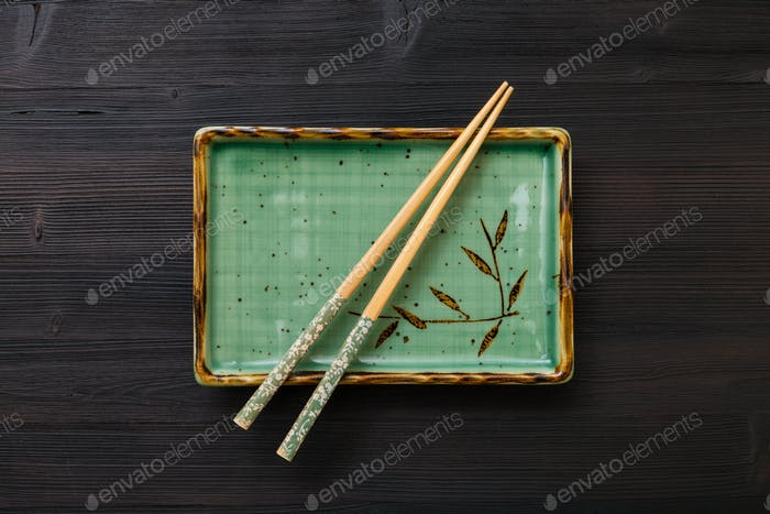 top view of square plate with chopsticks on brown