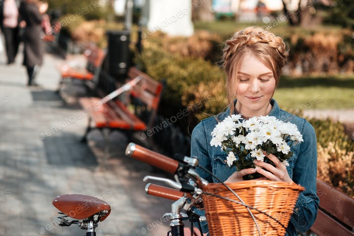 Charming woman with bicycle holding bouquet of flowers on bench