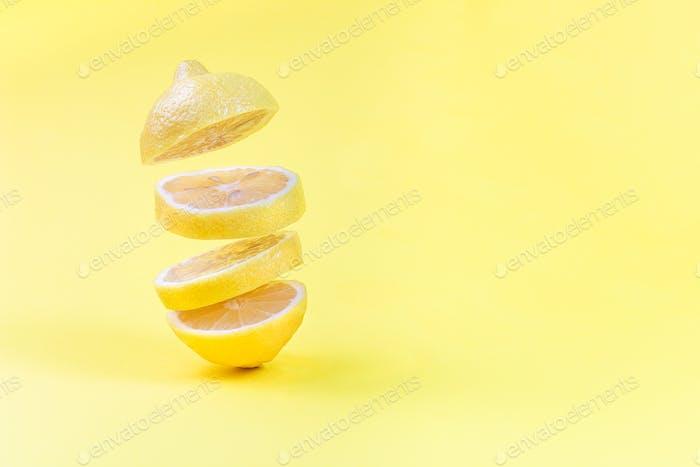 Lemon slices levitation on yellow background, horizontal, copy space