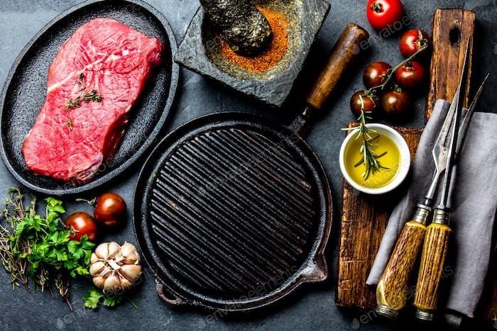 Rohes frisches Fleisch Steak Rinderfilet, Kräuter und Gewürze um Bratpfanne Teller