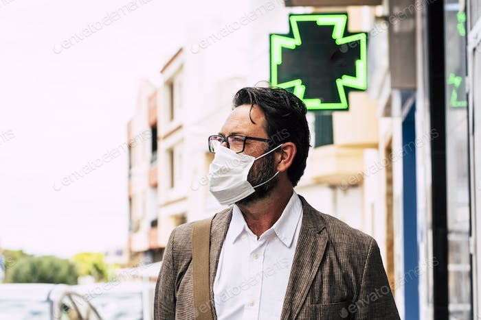 Adult man walking on the street wearing medical mask outdoor for coronavirus covid-19