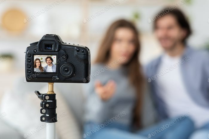 Selective focus on camera filming couple of bloggers