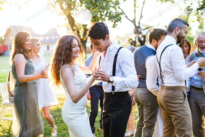 Guests dancing at wedding reception outside in the backyard.