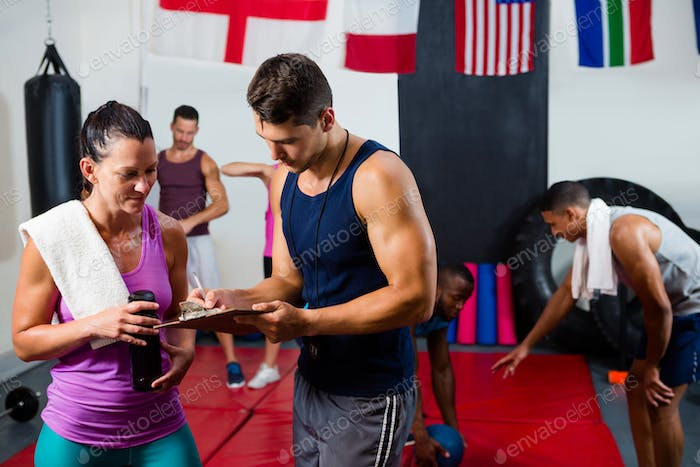 Male and female athletes discussing over clipboard