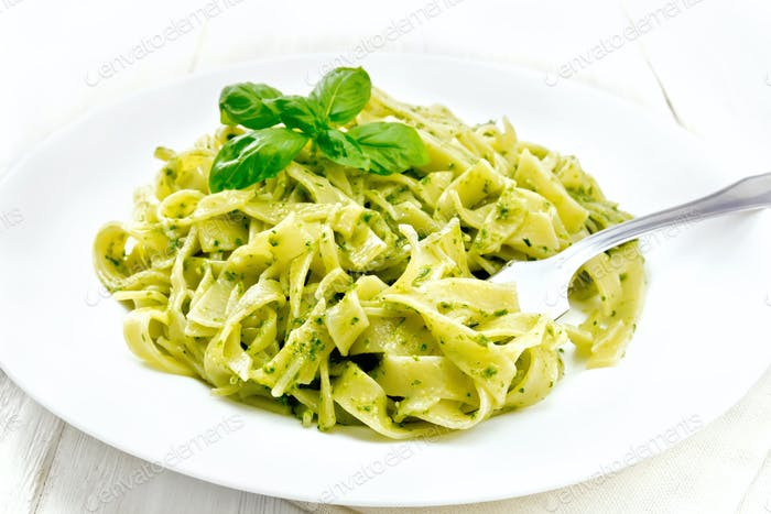 Pasta with pesto sauce in plate on light board