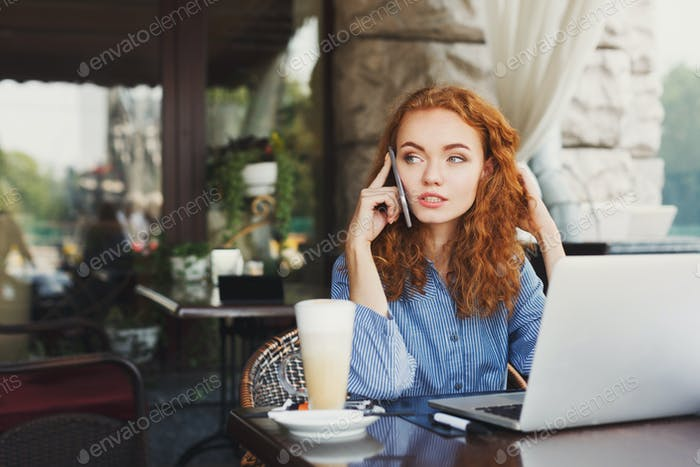 Young redhead woman talking on phone
