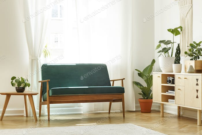 Real photo of a retro sofa next to a coffee table and cabinet wi