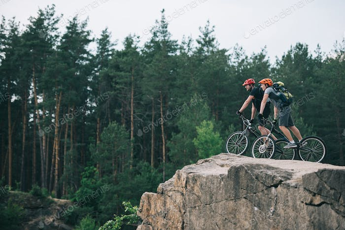 distant view of male extreme cyclists in protective helmets riding on mountain bicycles on rocky