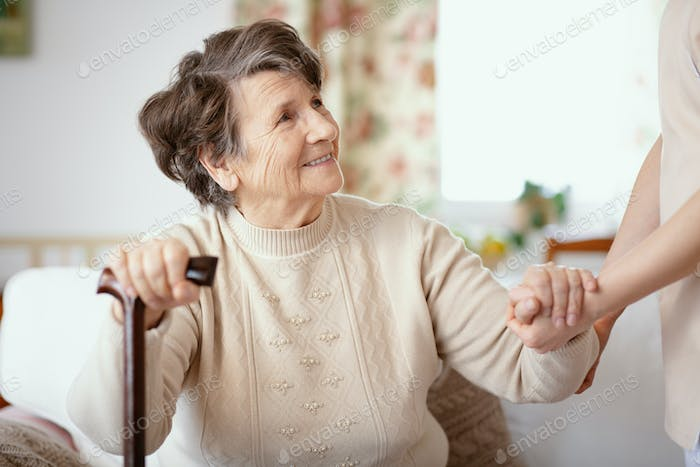 Smiling senior woman with walking stick and helpful caregiver ho