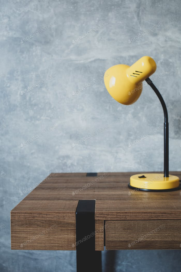 table lamp at wooden table near concrete grey wall