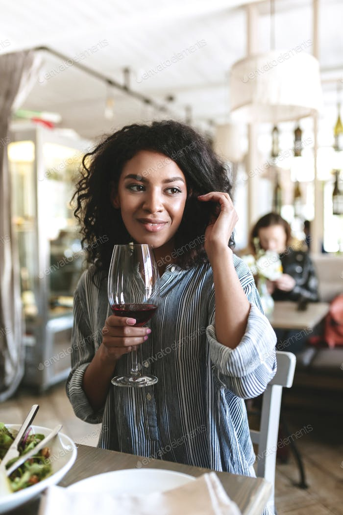 Young African American girl sitting in restaurant with glass of red wine in hand
