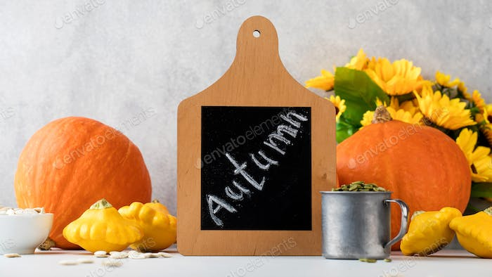 Chalk board with the inscription autumn surrounded by pumpkins and sunflowers. Autumn composition..