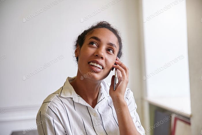 Pretty young dark skinned female with casaul hairsyle wearing striped white shirt, taking break