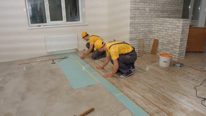 Men in the uniform laying laminate.
