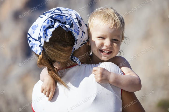 Happy toddler boy embracing mother and laughing
