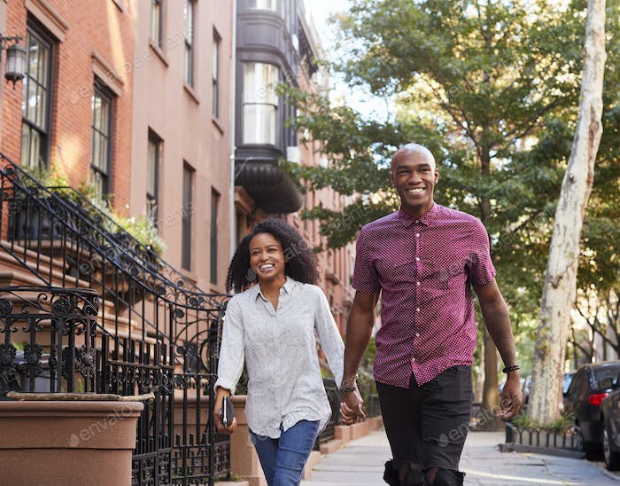 Young Couple Walking Along Urban Street In New York City
